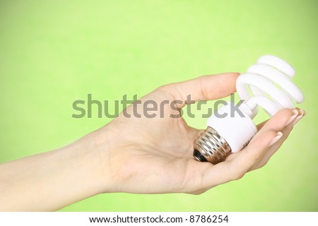 female hand holding a compact fluorescent energy saving environment friendly bulb on green background - stock photo