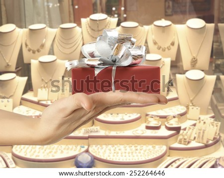Female hand holding a gift in the background jewelry shop window