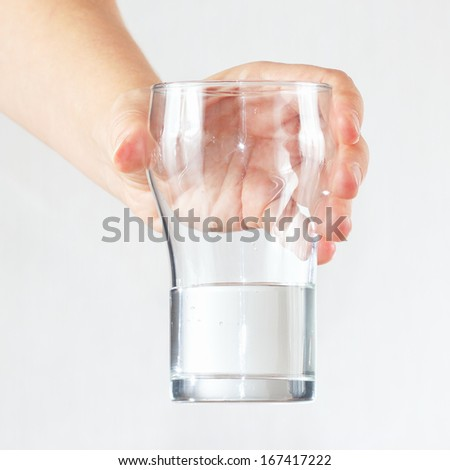 Female hand holding a glass of fresh water  - stock photo