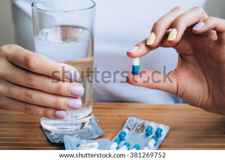 Female hand holding a glass of water and pill - stock photo