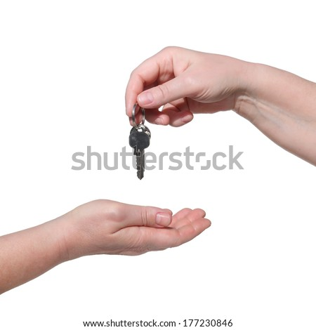 Female hand holding a keys and handing it over to another person. Isolated on the white background