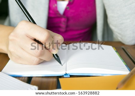 female hand holding a pencil to take notes - stock photo