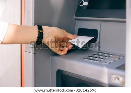 Female hand holding a receipt obtained from the ATM after withdrawing cash. The outer bank terminal. - stock photo