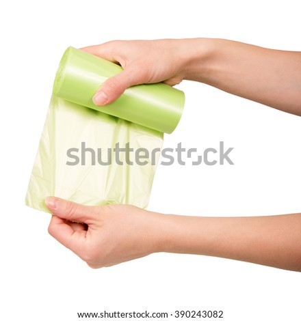 Female hand holding a roll of garbage bags isolated on a white background. - stock photo
