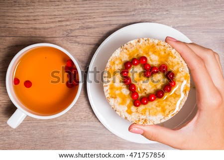 Female hand holding a sandwich of crispy bread, honey and cranberries, and cup with berry tea.