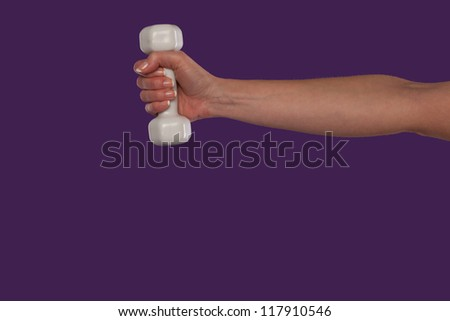 Female hand holding a small white dumbbell with the arm extended straight out over a purple studio background