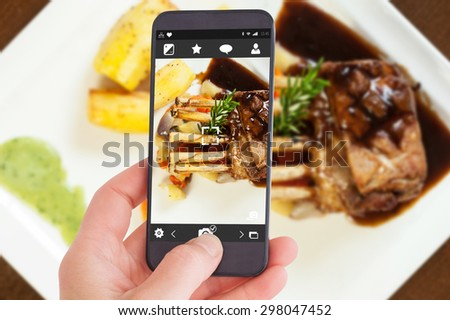 Female hand holding a smartphone against delicious rack of lamb dish with roast vegetable and potatoes - stock photo