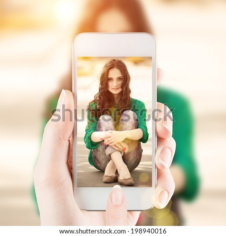 Female hand holding a smartphone and taking photo of beautiful young girl - stock photo