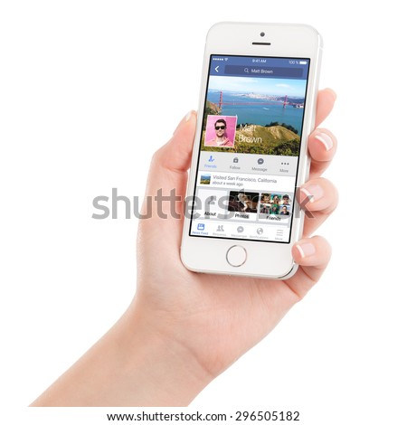 Female hand holding Apple Silver iPhone 5S with Facebook application on the screen. Facebook is an online social networking service. Isolated on white background. Varna, Bulgaria - February 02, 2015. - stock photo