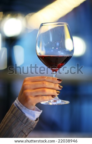Female hand holding big glass of red wine. Shallow DOF. - stock photo