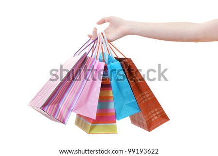 Female hand holding bright shopping bags isolated on white - stock photo