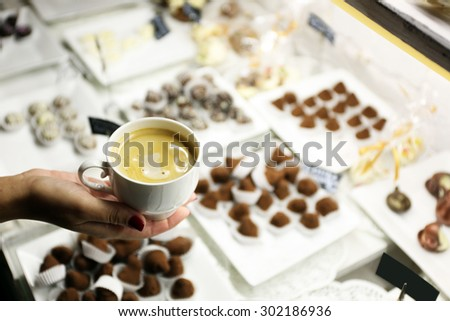 Female hand holding cup of coffee on table background - stock photo