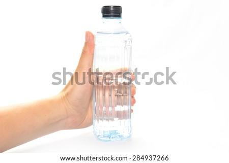 Female hand holding drinking water on white background - stock photo