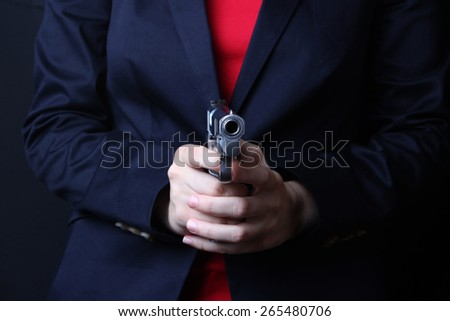 female hand holding gun with a black background  - stock photo
