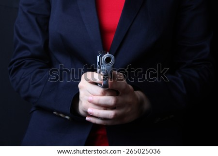 female hand holding gun with a black background çekilmil - stock photo