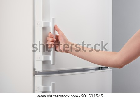 Female hand holding handle of white refrigerator door on gray background & Female Hand Holding Handle White Refrigerator Stock Photo (Royalty ...