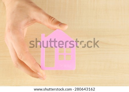Female hand holding house on wooden background