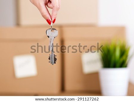 Female hand holding keys over pile of brown cardboard boxes with house or office goods background. Moving to new place of living concept. - stock photo