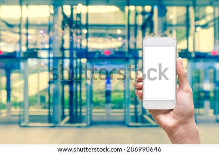 Female hand holding mobile smart phone on the Abstract blurred photo of glass elevation with bokeh background, business concept - stock photo