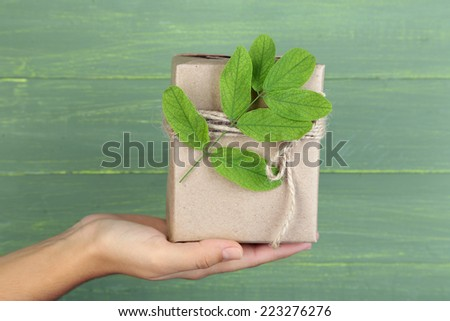 Female hand holding natural style handcrafted gift box with fresh leaves and rustic twine, on wooden background - stock photo