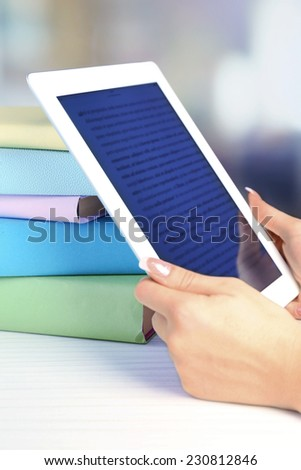 Female hand holding PC tablet near books, close-up. Modern  education concept - stock photo
