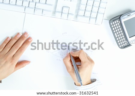 Female hand holding pen, drawing pie chart, beside desktop computer keyboard and mobile phone.