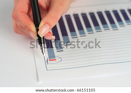 Female hand holding pen over business graph - stock photo