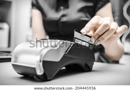Female hand holding plastic card in payment - stock photo
