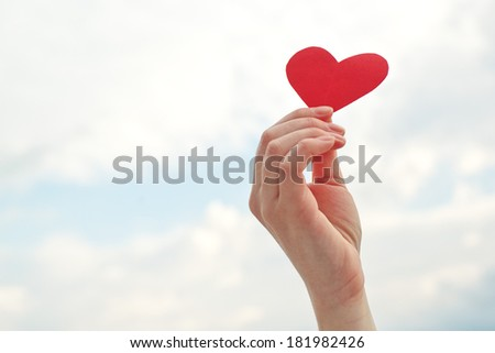 Female hand holding red paper heart raised up in the air. be my VAlentine concept. - stock photo