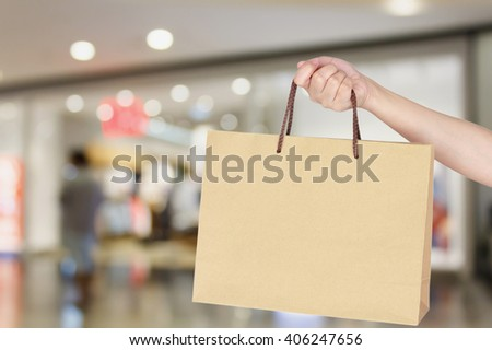 female hand holding shopping bag with shopping mall store blurred background - stock photo