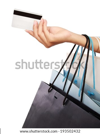Female hand holding shopping bags and credit card, isolated on white background