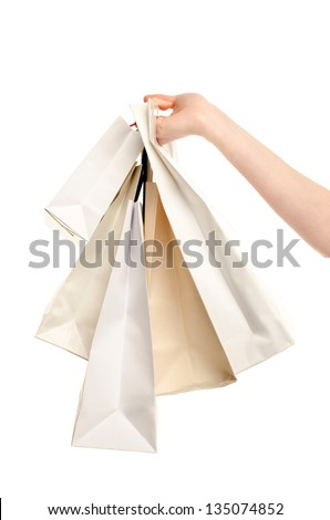 Female hand holding shopping bags. Hand of a woman holding many white shopping bags. Isolated on white. - stock photo