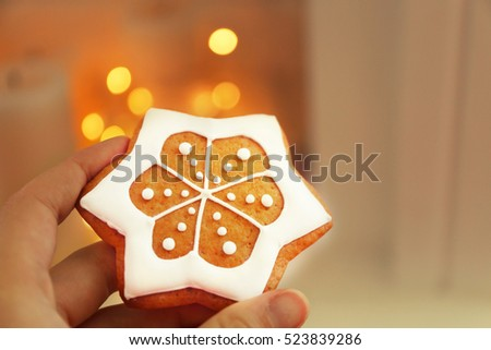 Female hand holding tasty gingerbread cookie on blurred background, close up view
