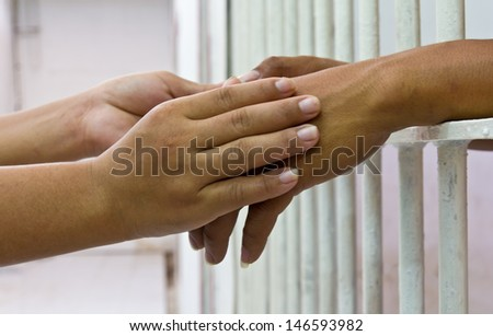 Female hand holding the hand of her husband, who was incarcerated in the prison bars of white. - stock photo
