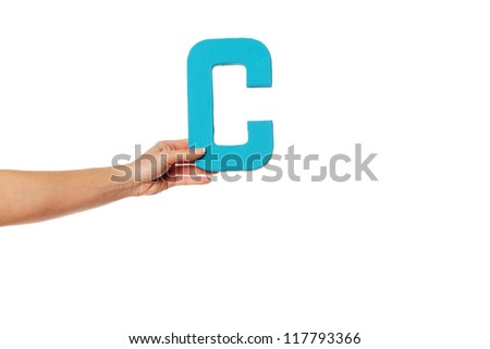 Female hand holding up the uppercase capital letter C isolated against a white background conceptual of the alphabet, writing, literature and typeface - stock photo