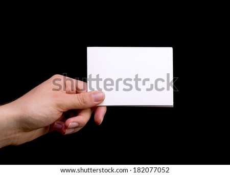 Female Hand Holding White Blank Card on Black Background - stock photo