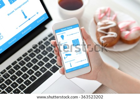 female hand holding white phone with program smart home on the screen against the background of the computer - stock photo