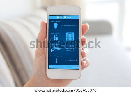 female hand holding white phone with smart home on the screen in the room - stock photo