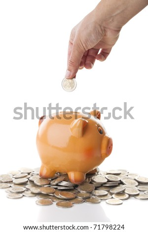 Female hand inserting a two Euros coin on a Piggy bank isolated over a white background - stock photo