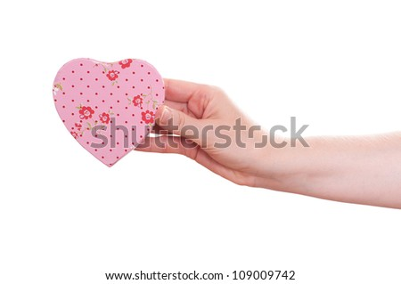 Female hand is holding a pink heart with flowers - stock photo