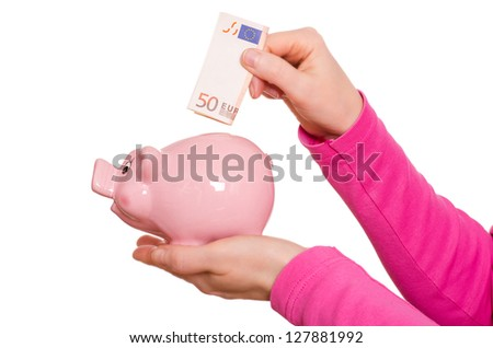 Female hand is putting a euro not into a pink piggy bank - stock photo