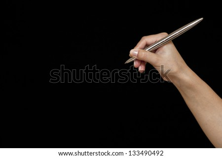 Female hand is ready for drawing with black marker. Isolated on black - stock photo