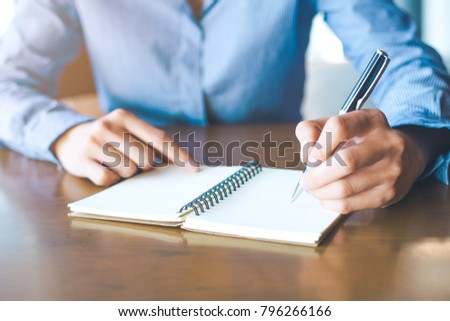 Female hand is writing on notepad with pen in office.