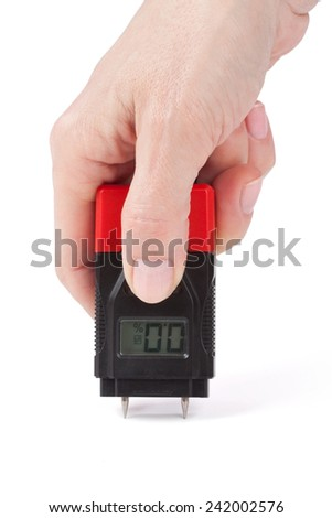 Female hand measuring moisture in wall over white - stock photo