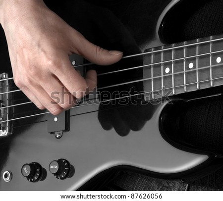 female hand on the detail of a black bass guitar in dark back - stock photo