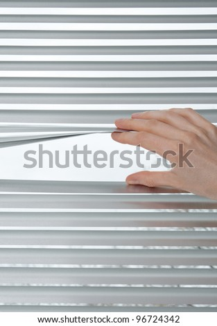 Female hand opening metallic venetian blinds for peeking.