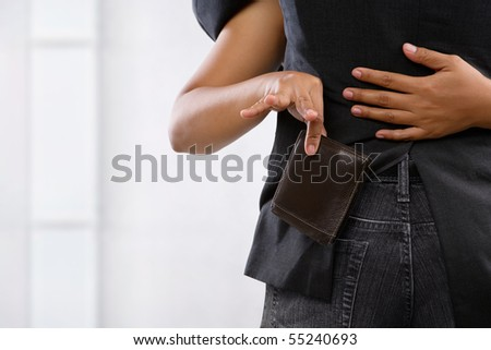 female hand picpocketing wallet from businessman's pocket, a concept for money thief - stock photo