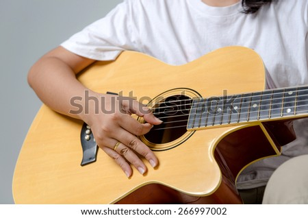 Female hand playing music by acoustic guitar - Close up shot and soft focus - stock photo