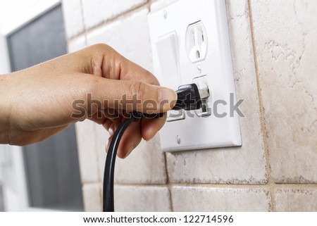 Female hand plugging in appliance to electrical outlet in wall - stock photo