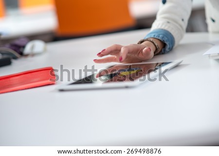 Female hand pointing a finger on a tablet - stock photo